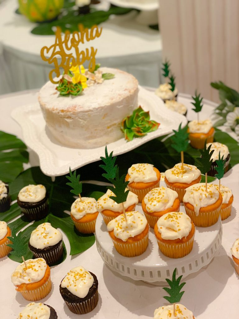 tropical dessert table with pineapple cupcakes and white cake