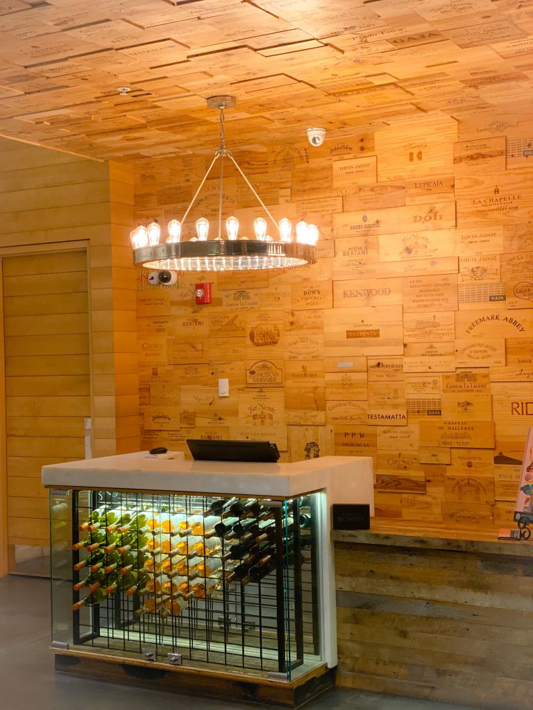 lobby area of epicurean hotel with bottles of wine under front desk