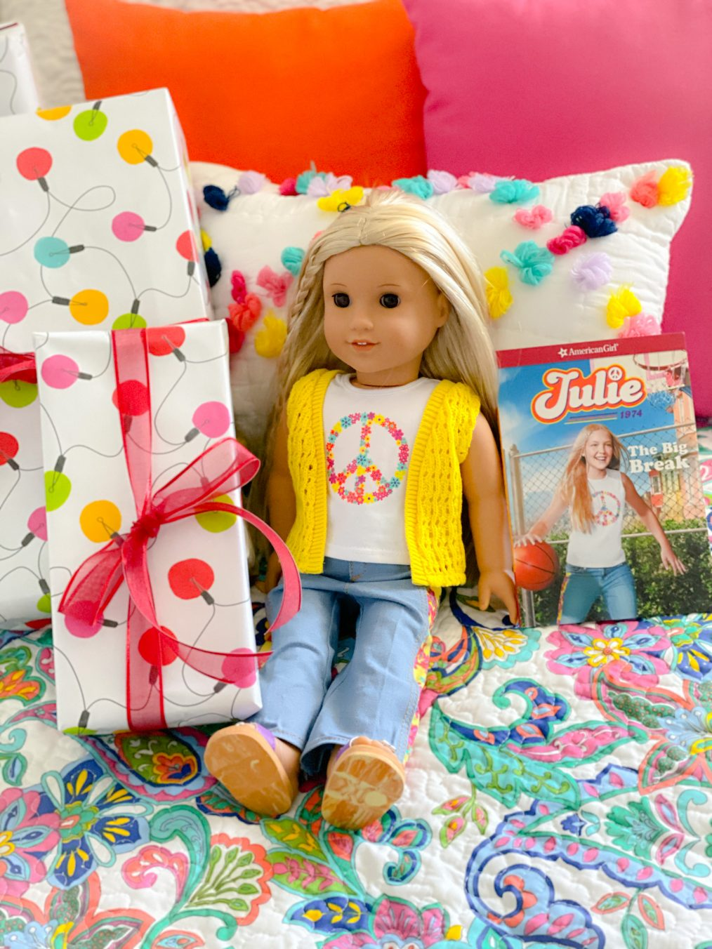 American Girl Julie in yellow crochet vest and bellbottoms surrounded by holiday lights wrapped gifts