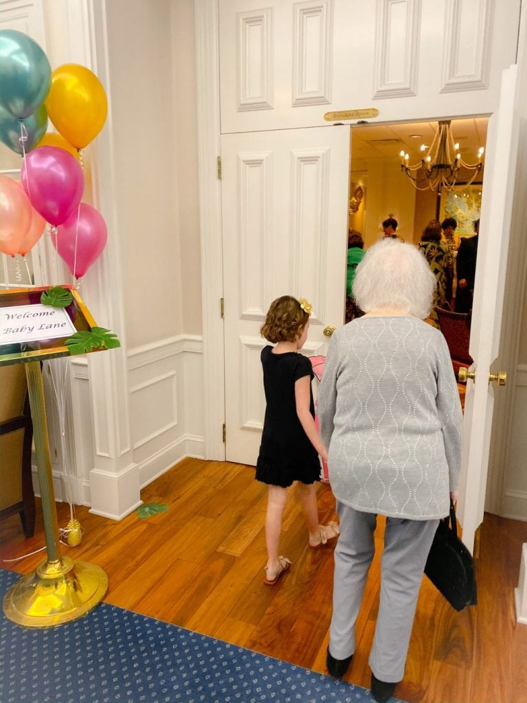 little girl holding hands with elderly woman walking through a door