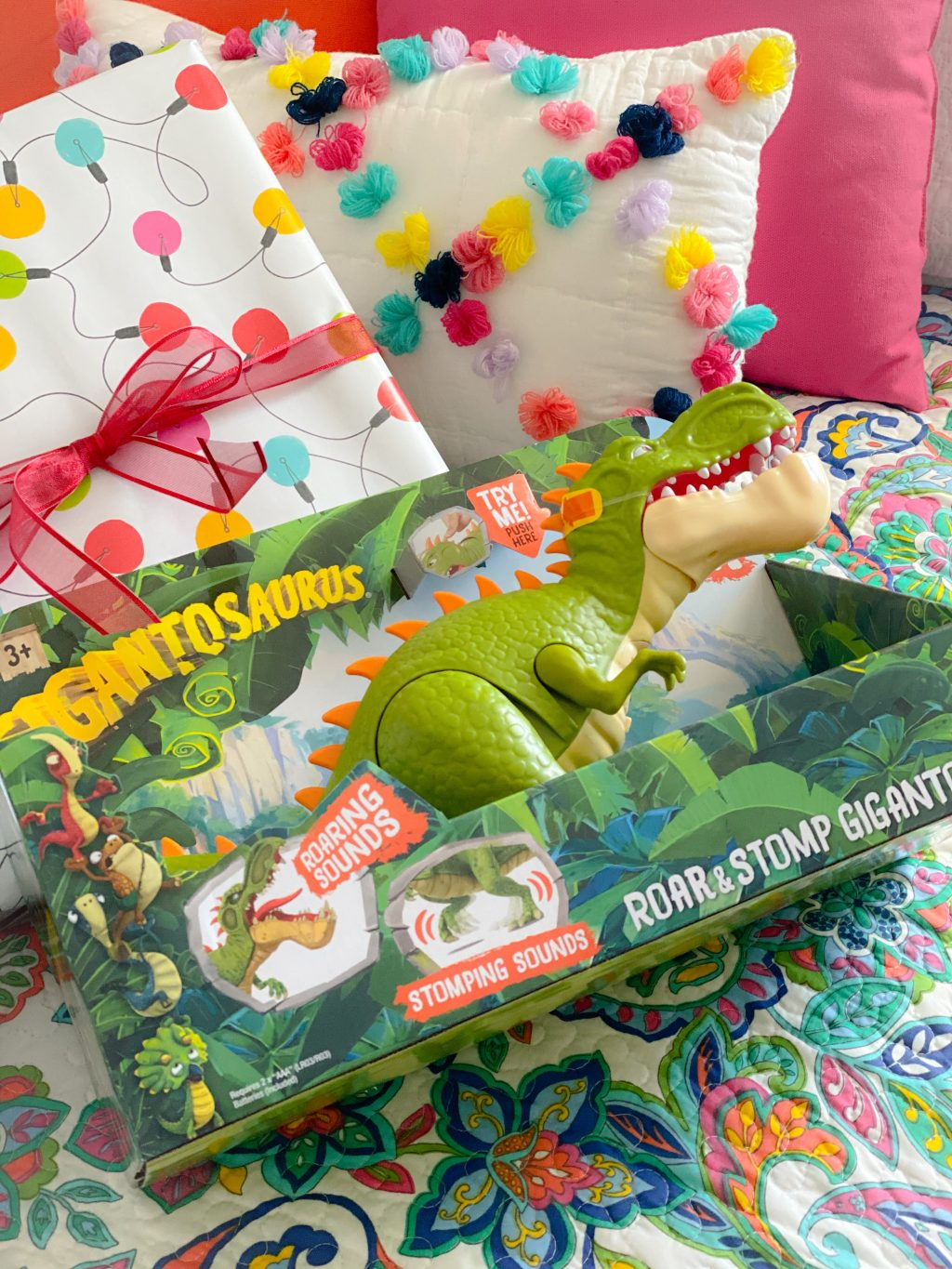 dinosaur toy with brightly wrapped holiday gifts
