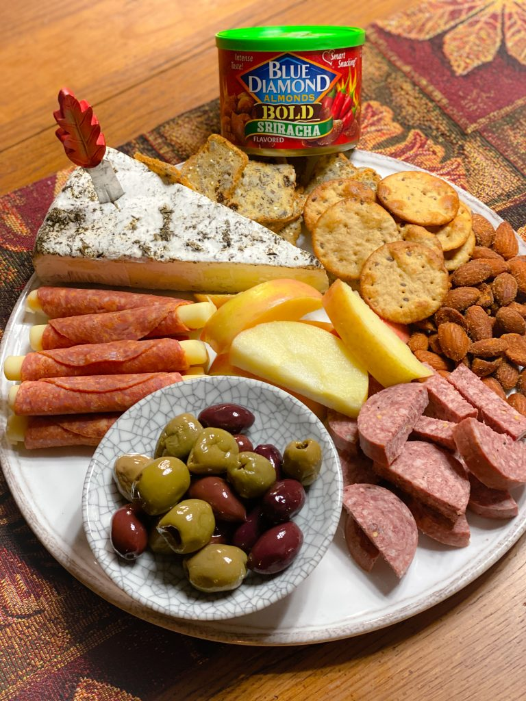 sausage, cheese, olives, almonds and crackers on white platter