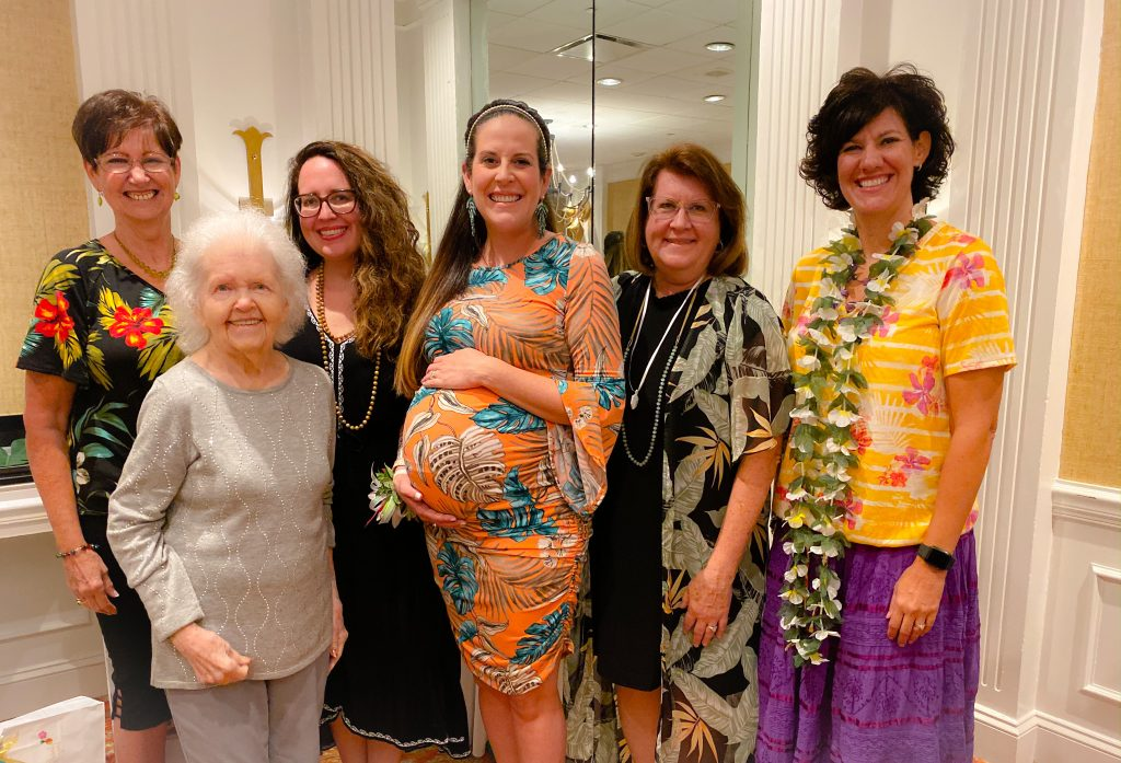 women standing with pregnant woman in tropical print maternity dress