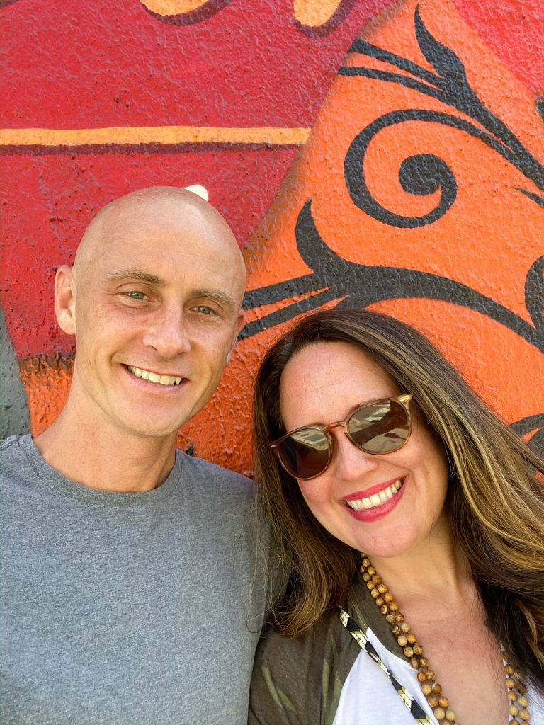 bald man and woman with long dark hair standing in front of red and orange mural