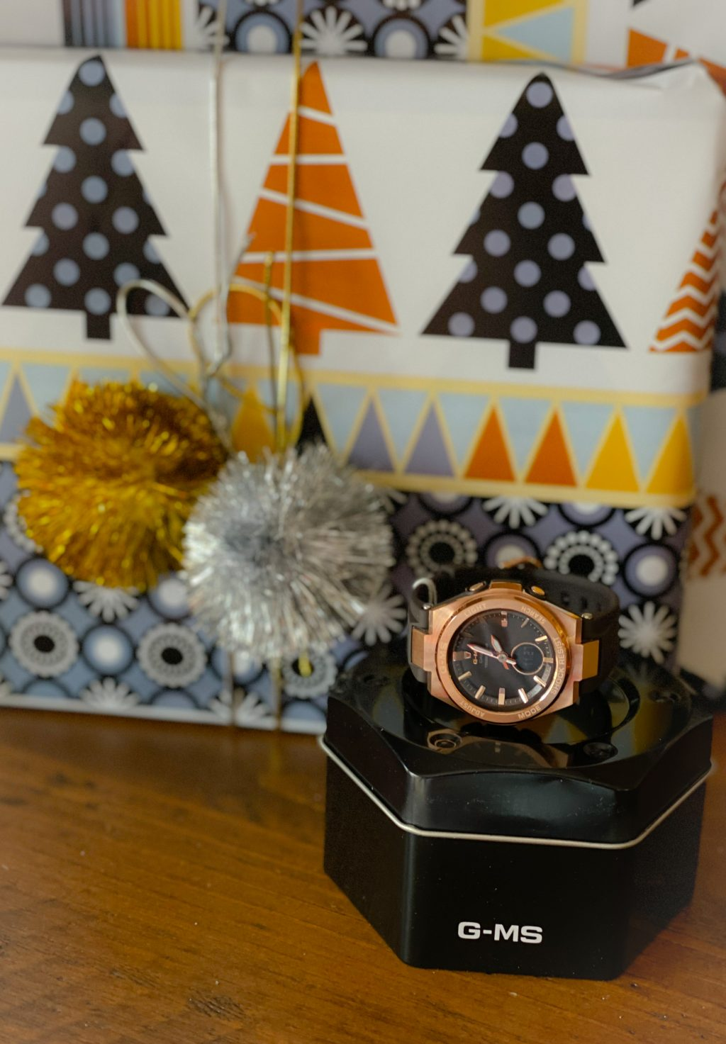 rose gold baby g watch next to metallic wrapped gifts