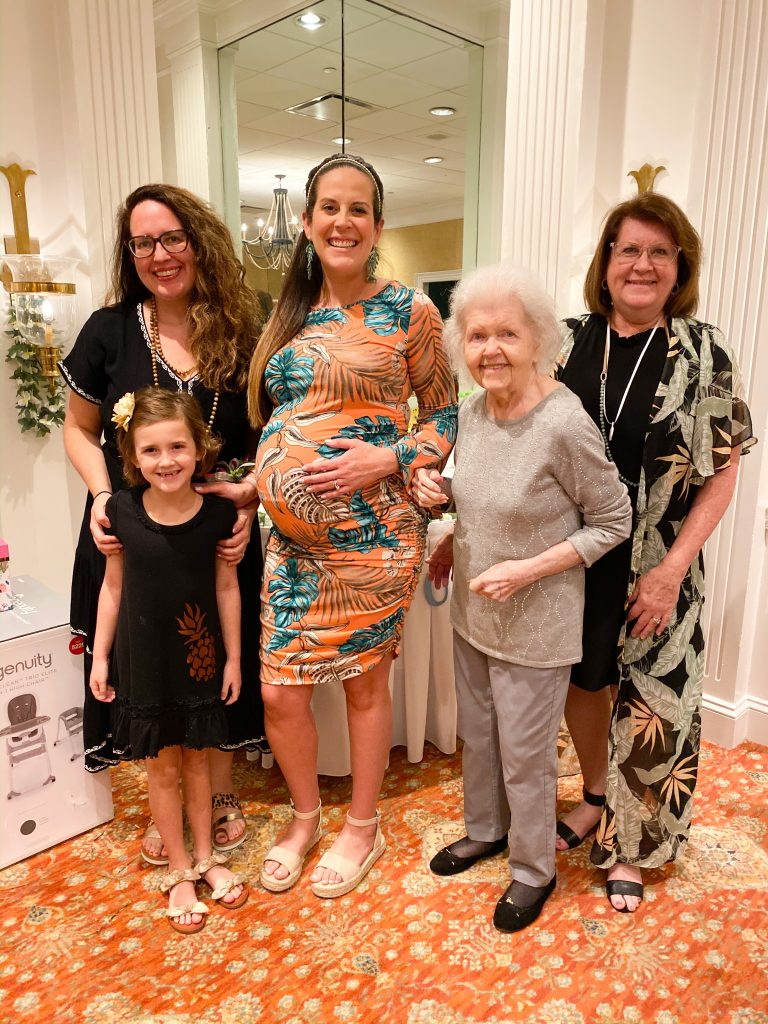 four generations of women posing with pregnant woman