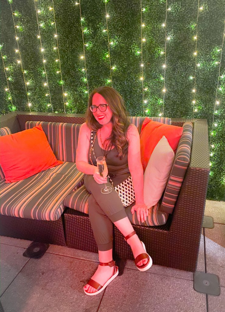woman wearing green jumpsuit sitting on striped couch holding a glass of champagne in front of a wall of lights