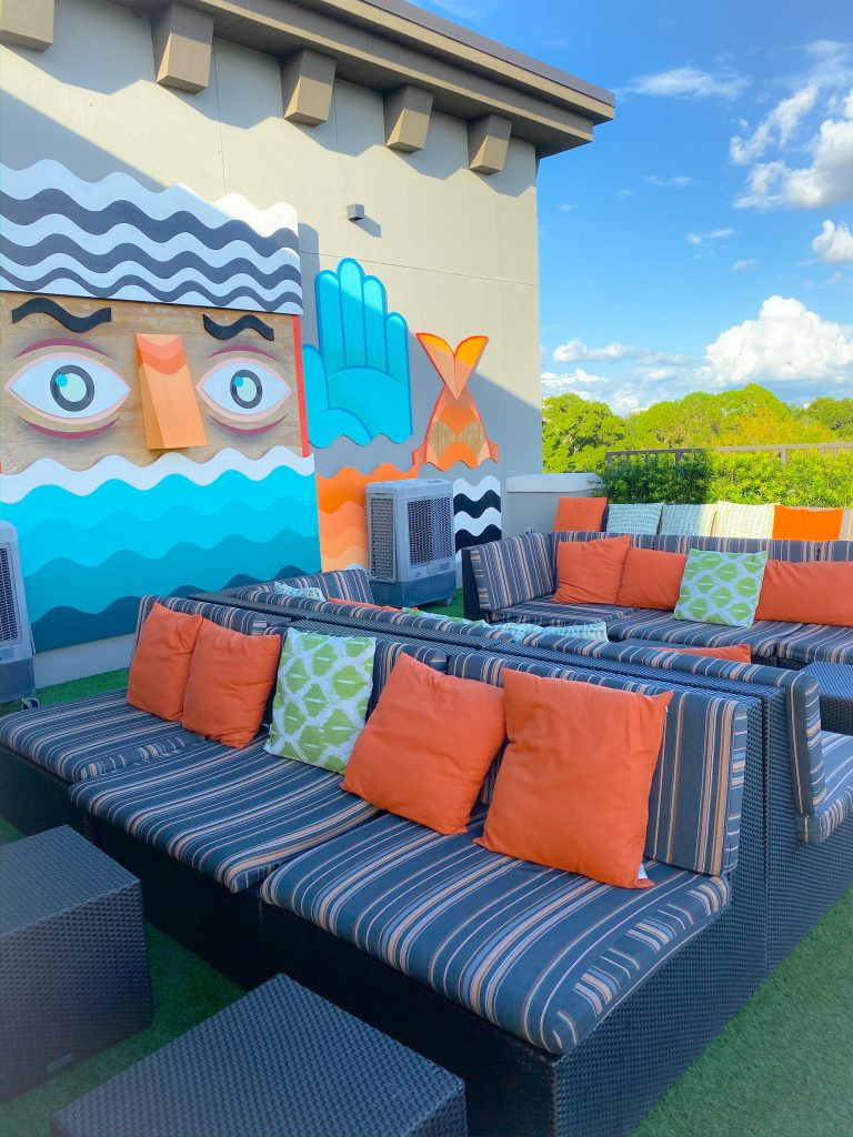 striped couches with orange pillows on rooftop deck