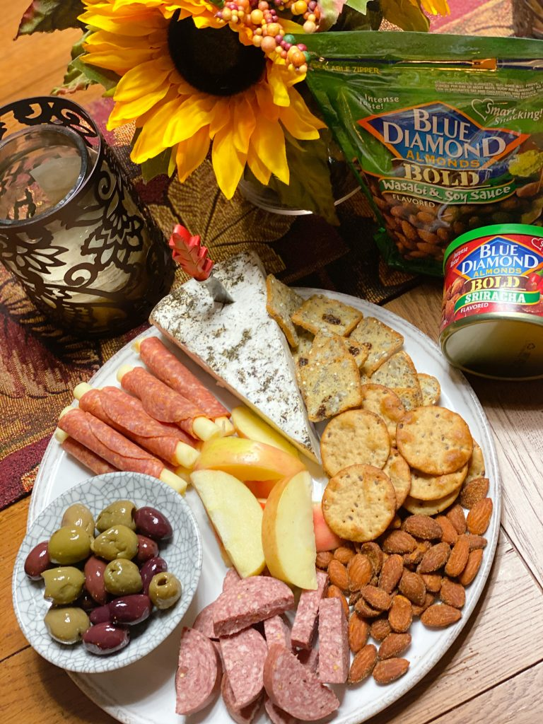 thanksgiving charcuterie board with blue diamond almonds, cheese, sliced meats, olives, crackers and apples