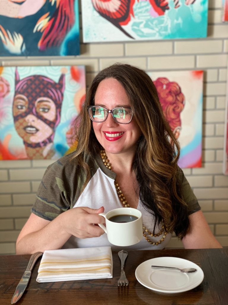 woman with long brown hair drinking a cup of coffee in front of a white brick wall with colorful paintings on it
