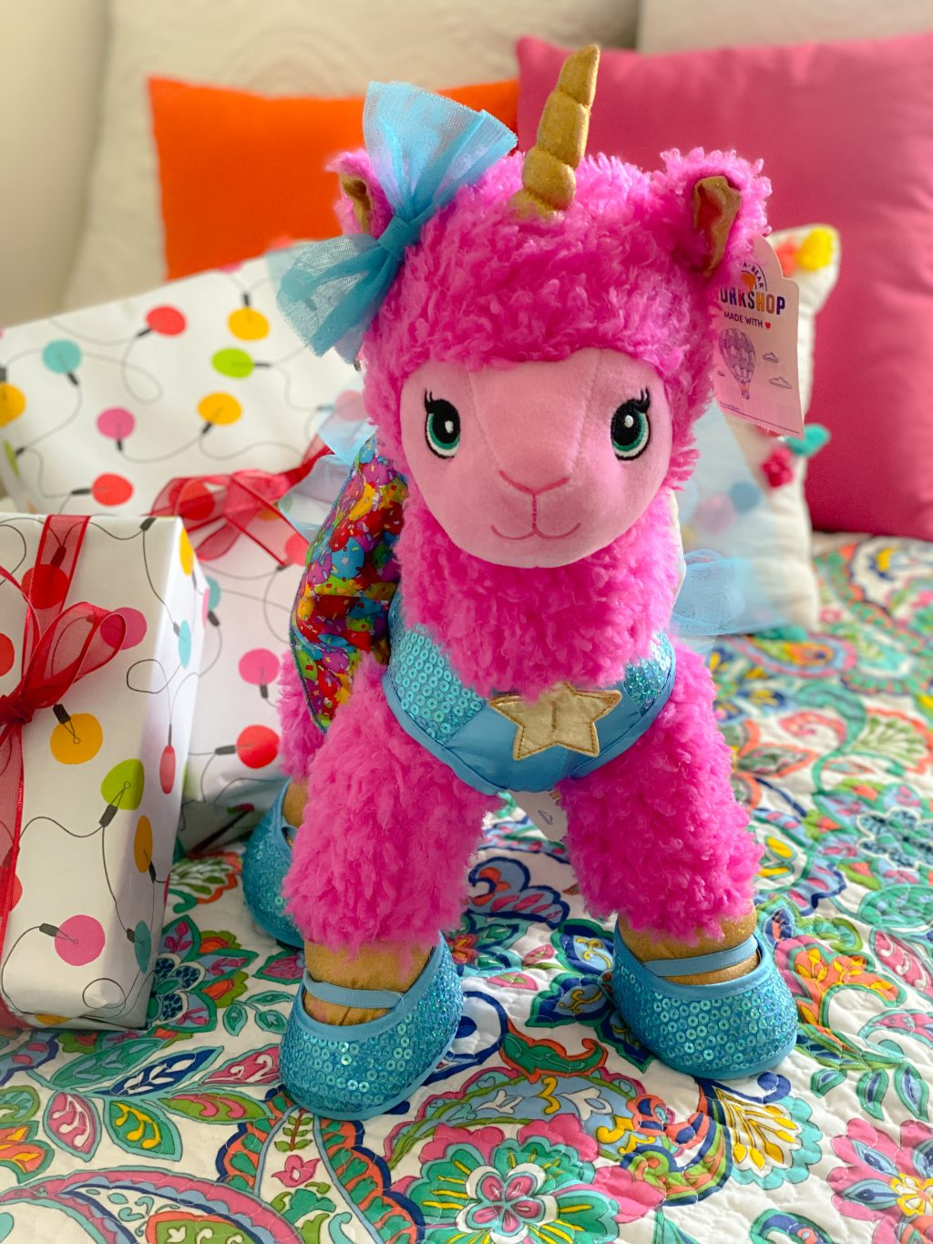 pink unicorn stuffed animal with white and red wrapped boxes