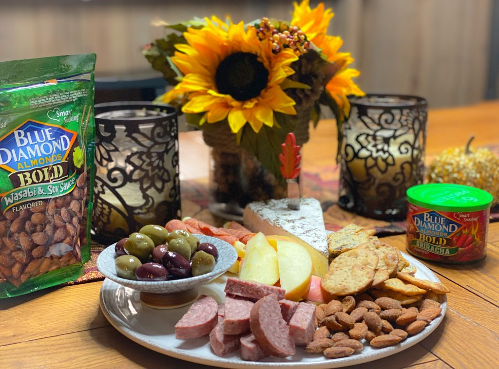 fall charcuterie board setup with sunflowers, candles and fall table runner