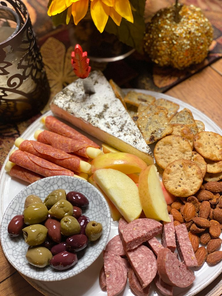pepperoni, brie, pita crackers, summer sausage, olives and spicy almonds on white plate