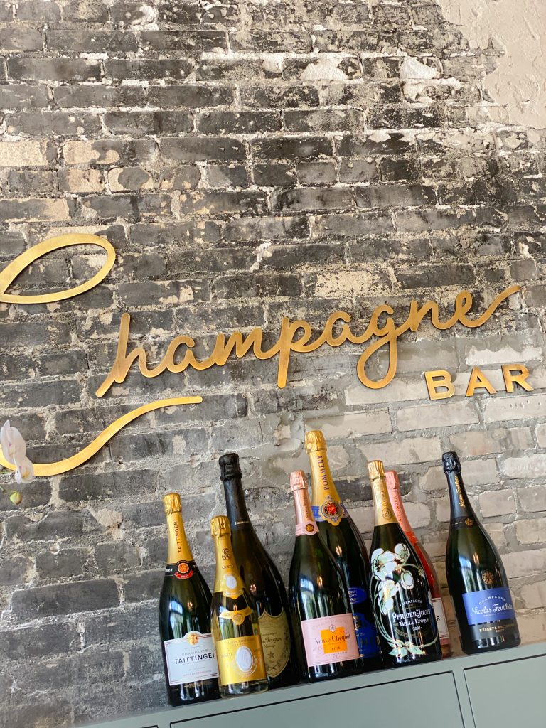 gold champagne bar sign on brick wall