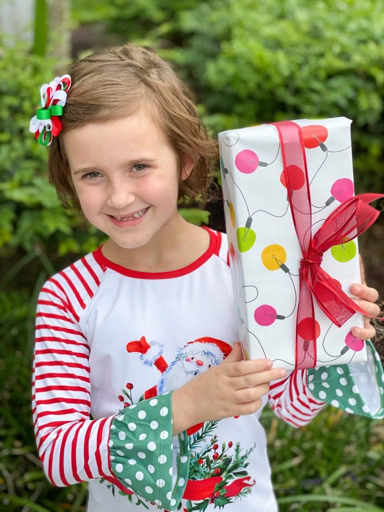 little girl with santa dress holding christmas gift