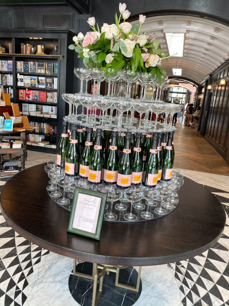 champagne bottles with flutes piled on top