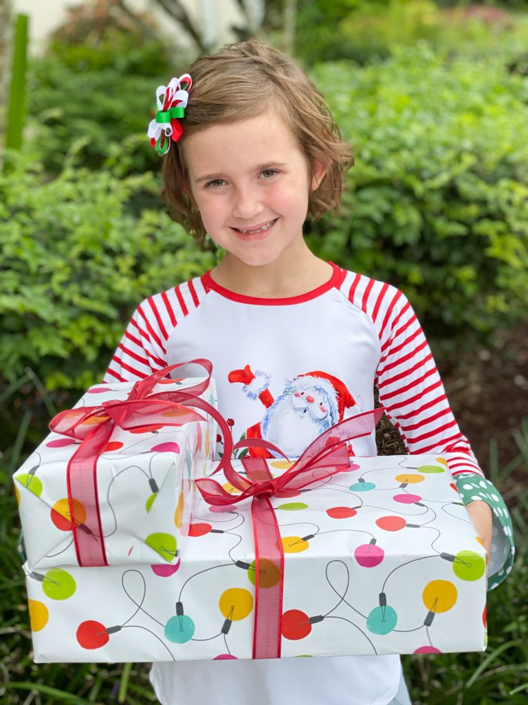 little girl in red and white striped dress holding two wrapped christmas gifts