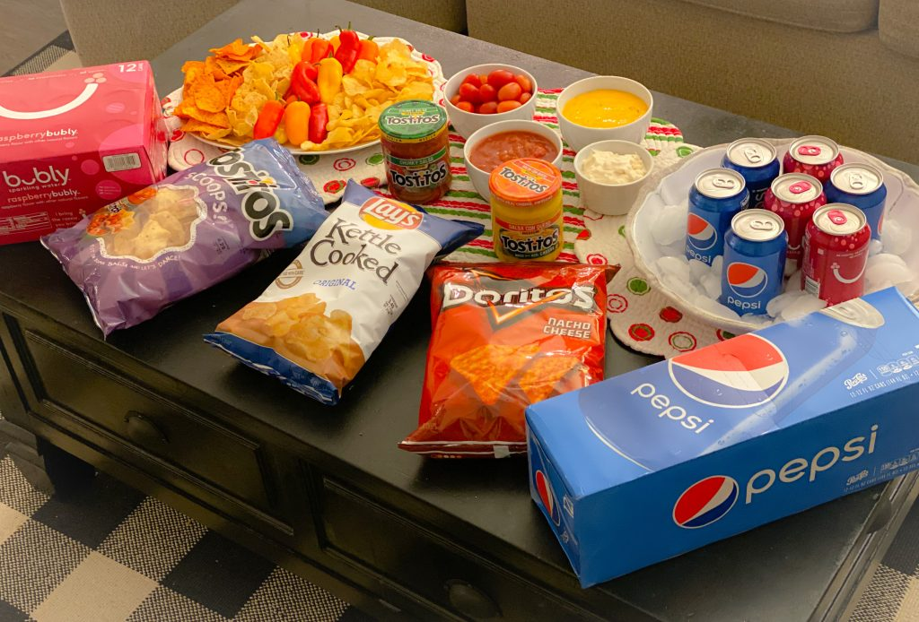 chips, dip and soda on table