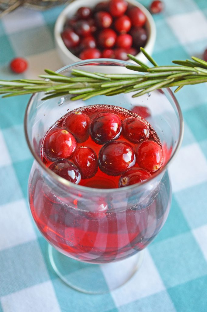 cranberry mimosa in clear flute on turquoise and white checked tablecloth