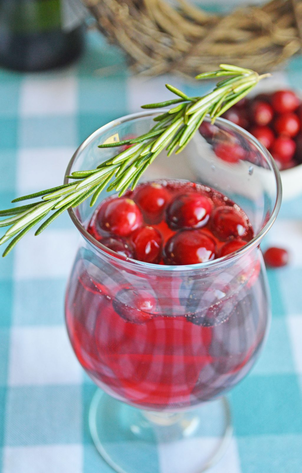 cranberry mimosa with sprig of rosemary on top