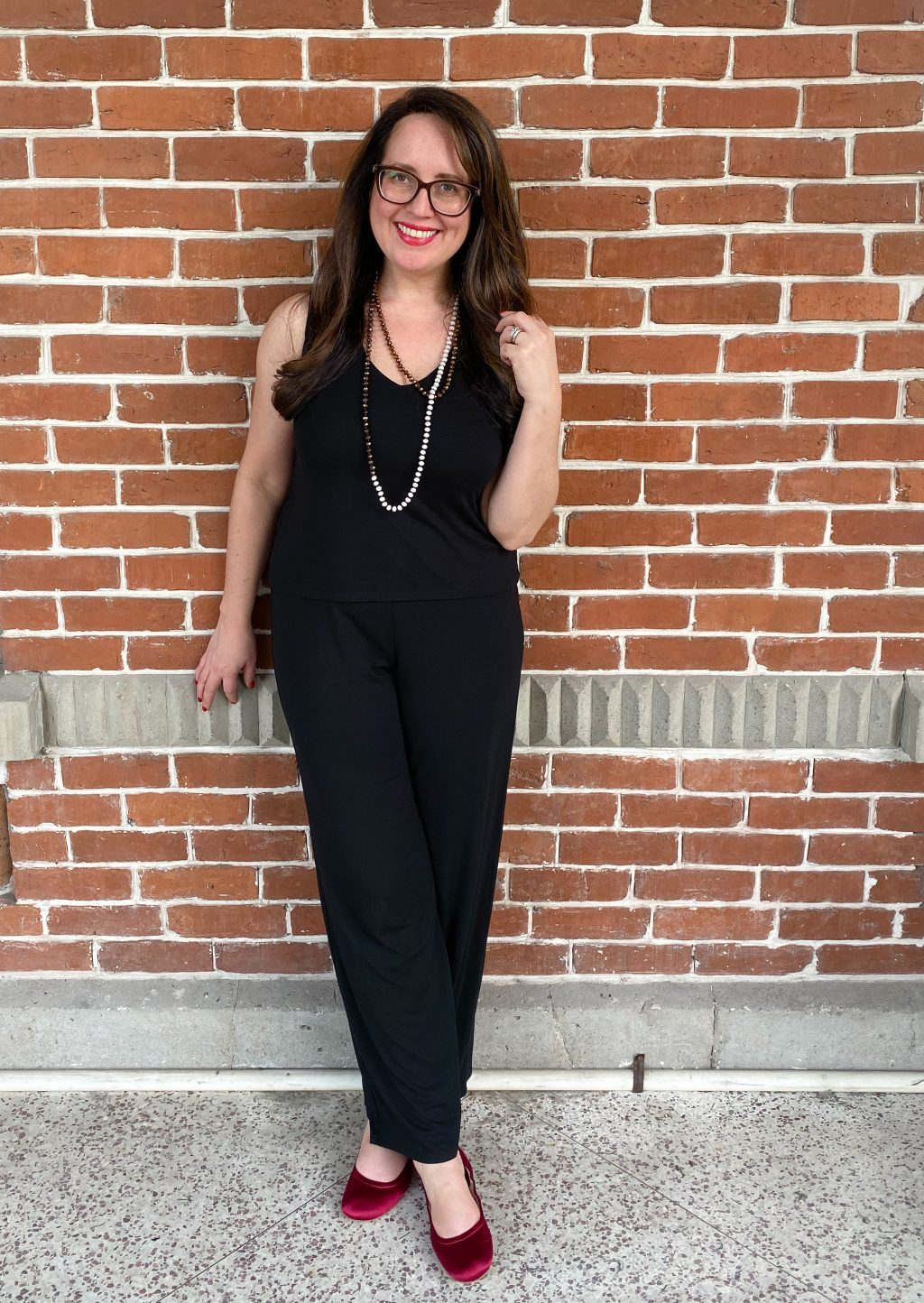 brunette woman wearing black jumpsuit standing in front of brick wall