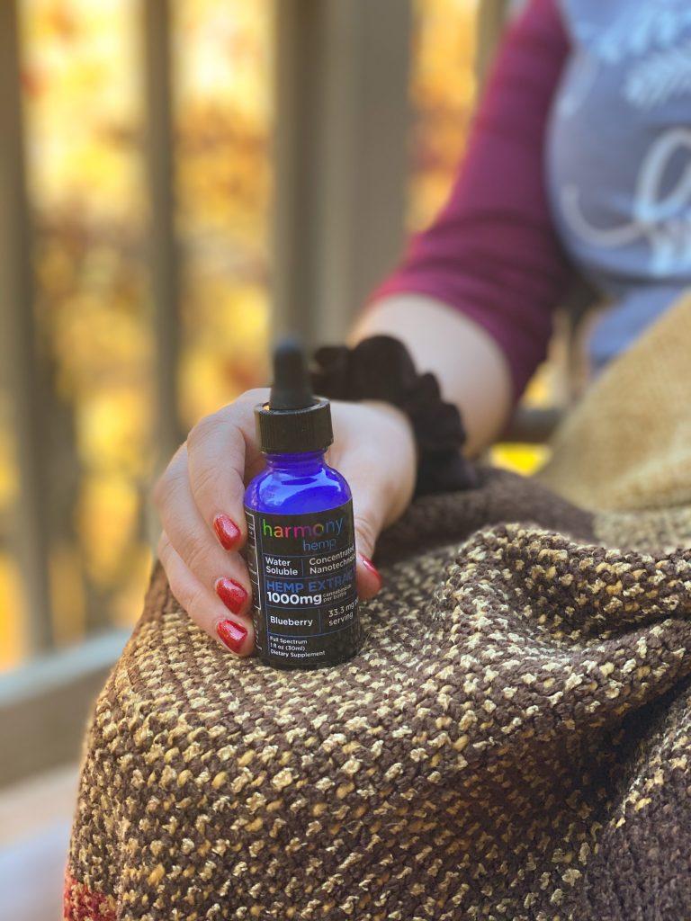 blue bottle of cbd oil on plaid blanket