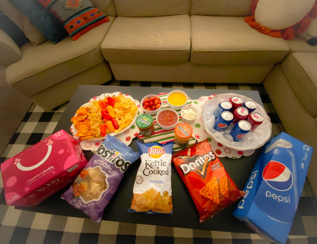 football game watching appetizers like tositos, doritos, chips and dip on black coffee table