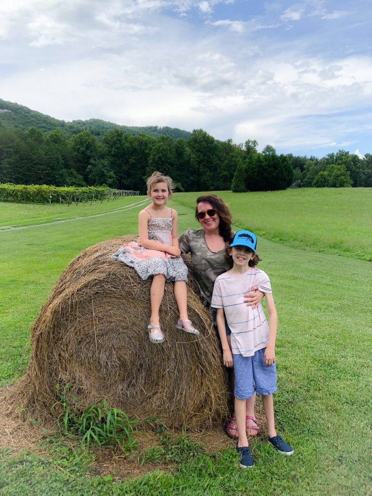 mom, son and daughter next hay bale