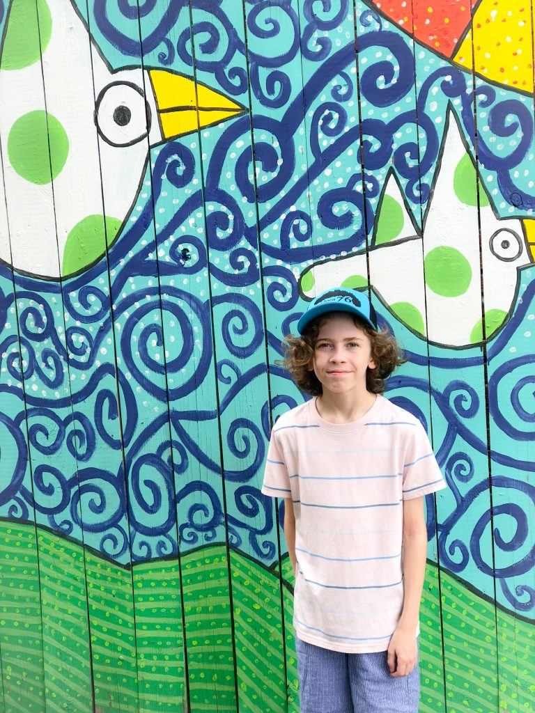tween boy in pink shirt standing in front of blue and green mural