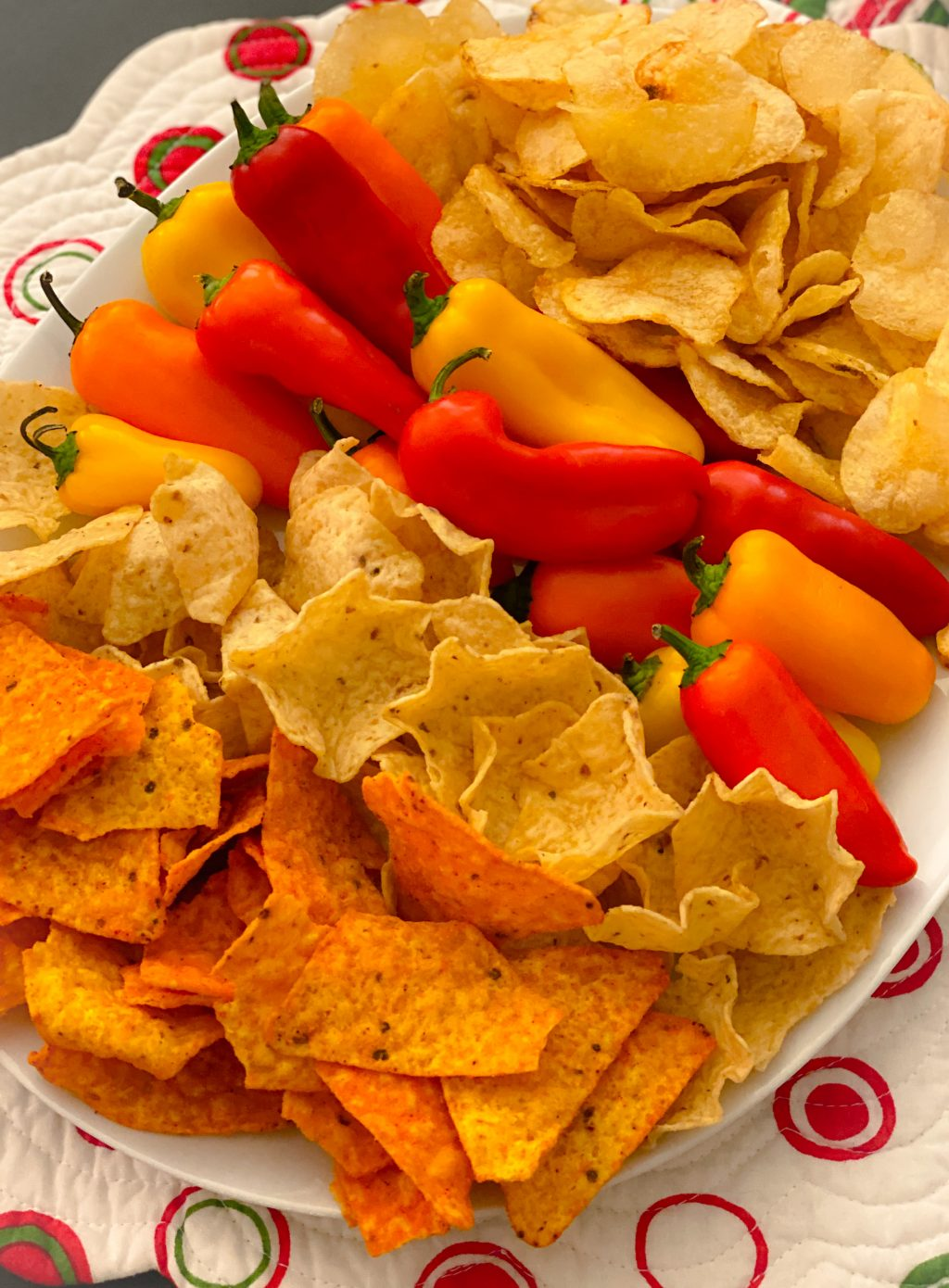 chips and peppers on white try