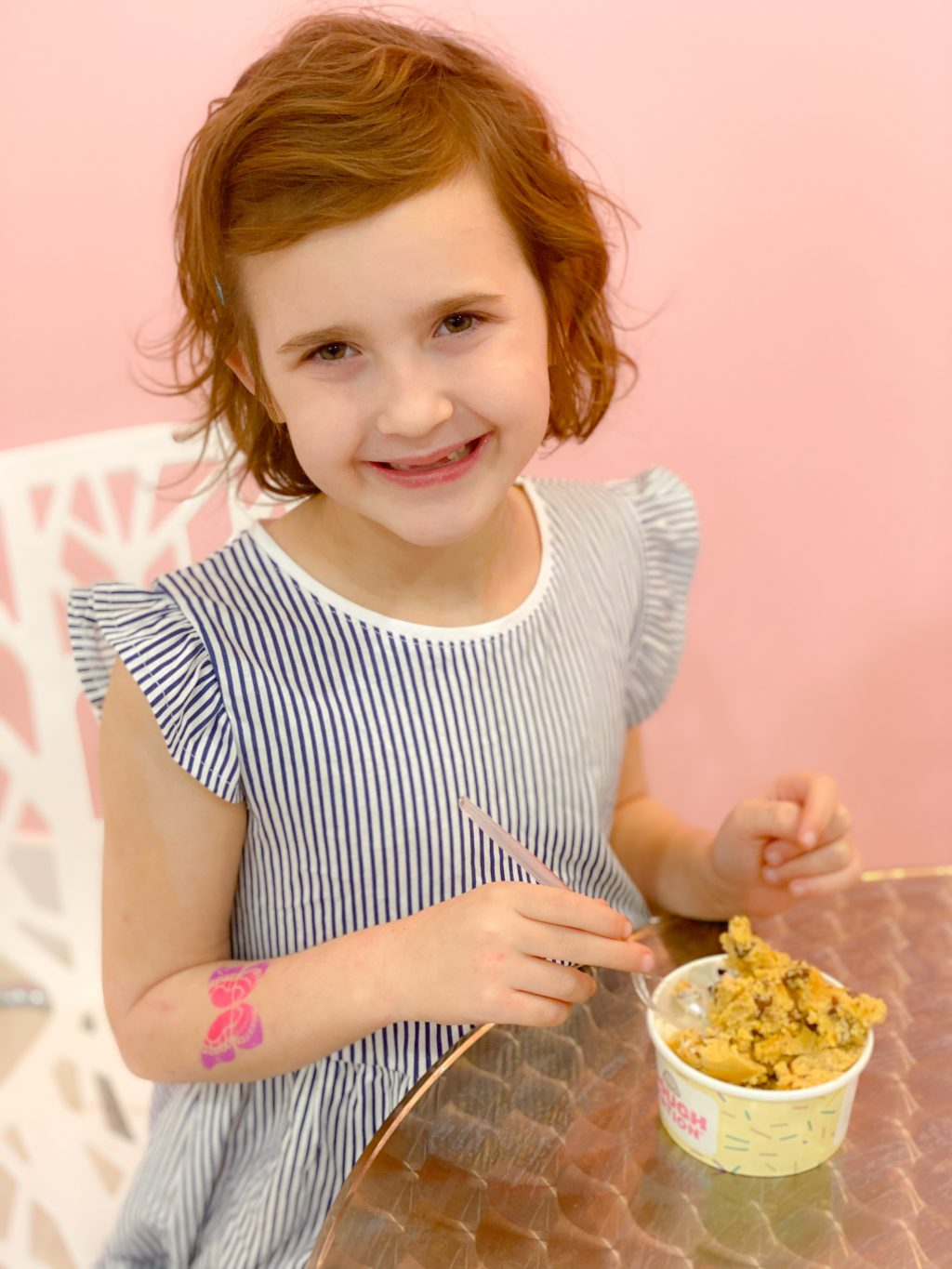 little girl in blue striped dress eating cookie ough