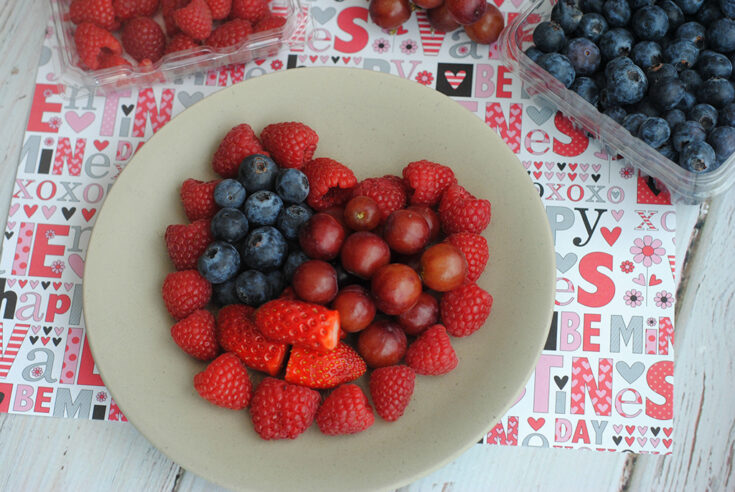 strawberries, raspberries, blueberries and grapes in heart shape on white plate