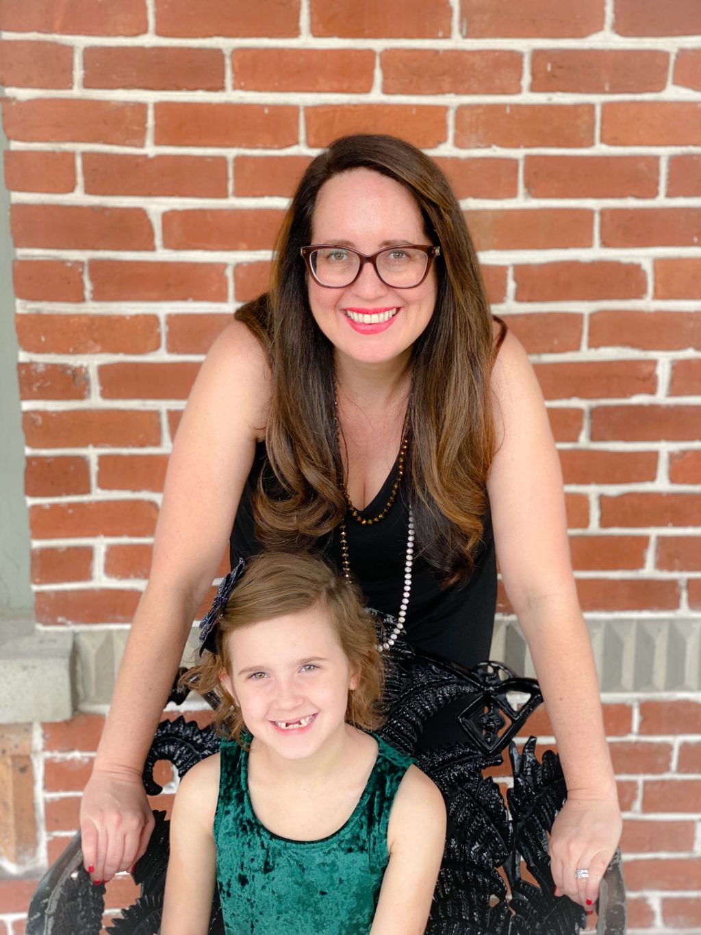 mom and daughter posing in black dresses and glasses