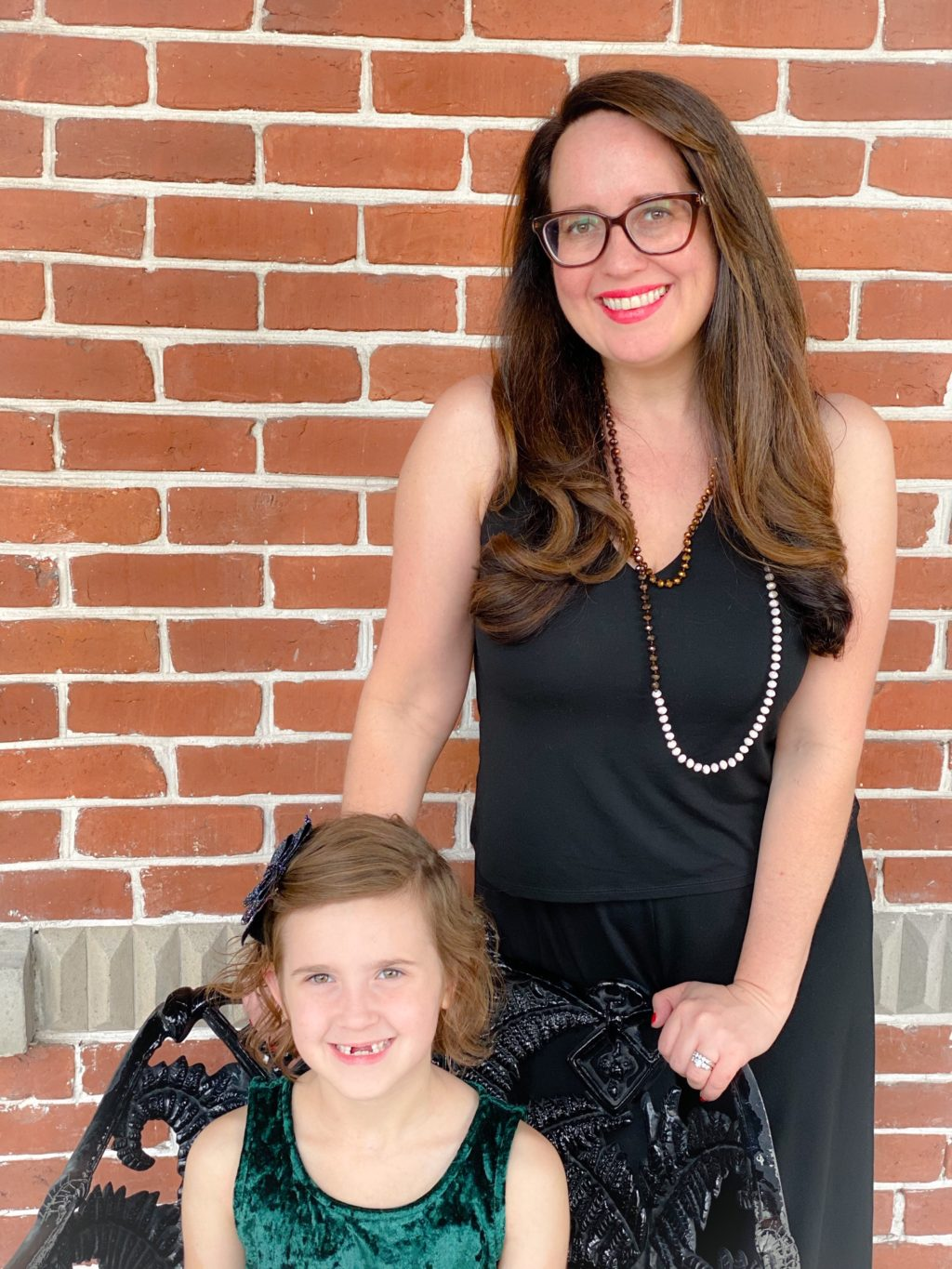 young mom wearing glasses and black jumpsuit