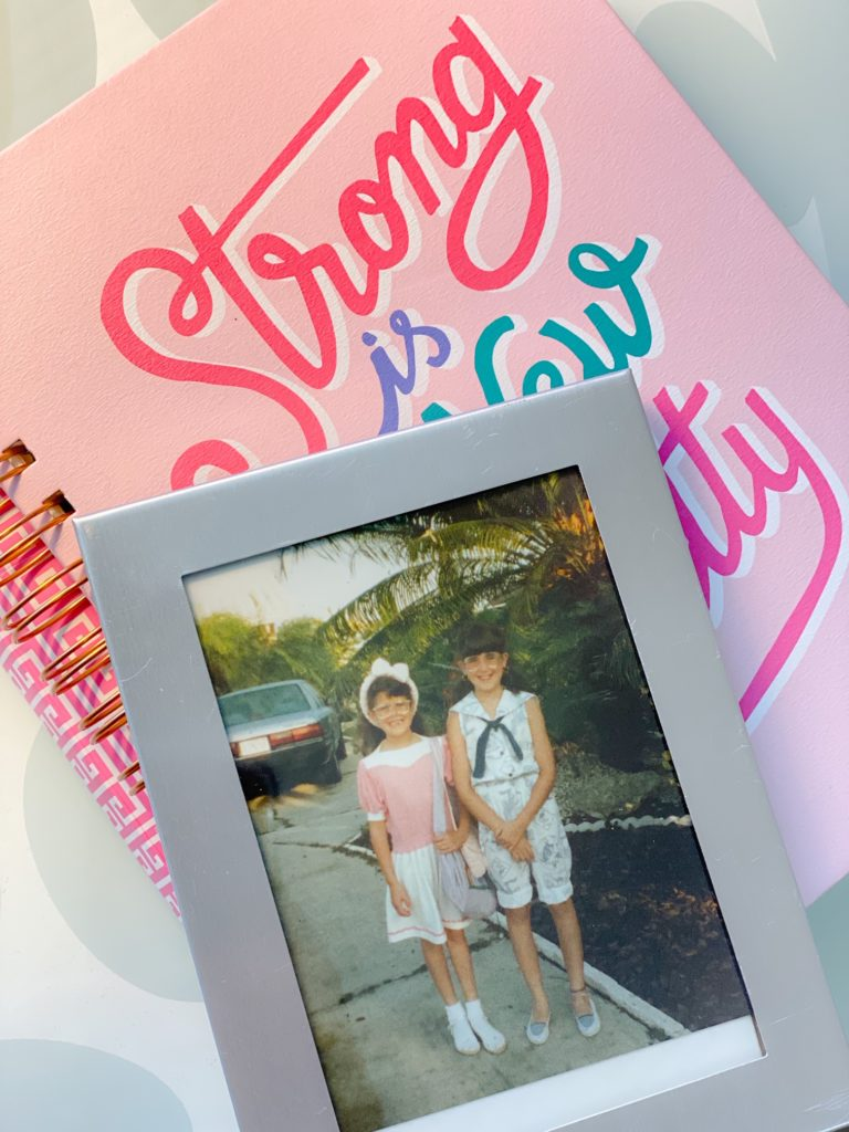 framed photograph of little girls on top of pink notebook