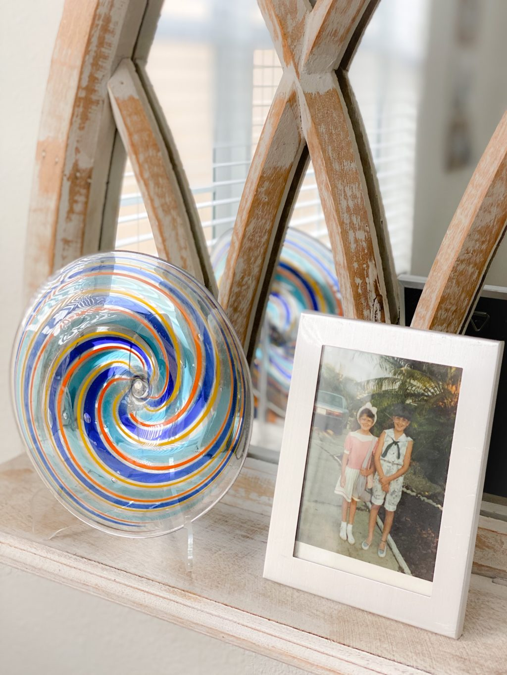 silver framed photograph on mirrored shelf