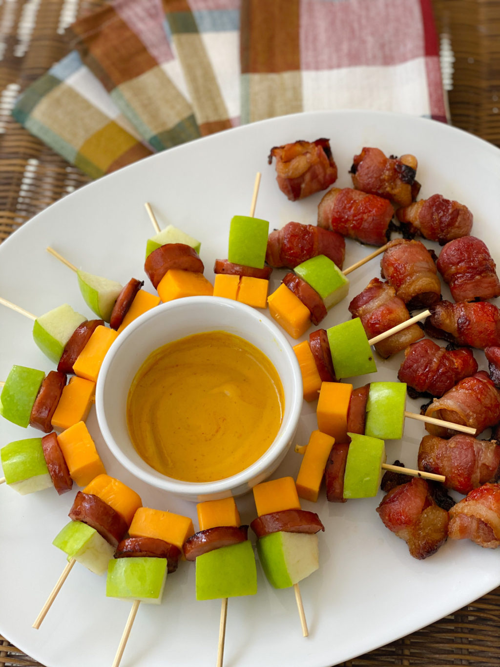 sausage and hot dog appetizers on white plate and plaid placemats