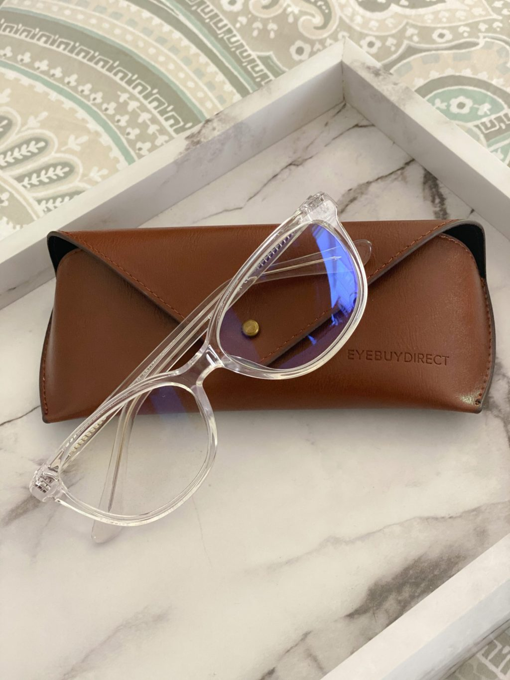 clear blue blocking glasses on brown glasses case on white marble tray