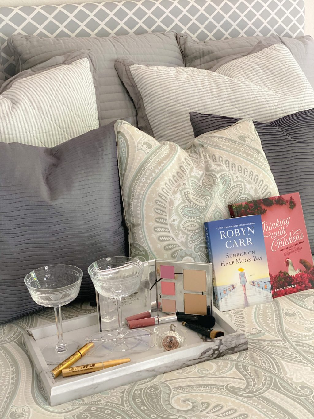glasses, books, makeup palette, pink lip gloss, gold lash serum bottles, black make brushes, clear watch and clear glasses on white and gray bed