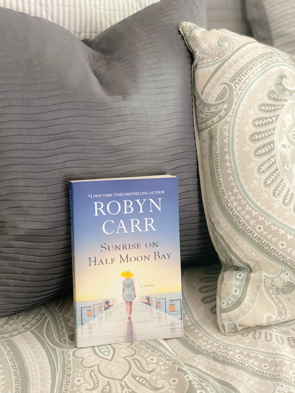 blue and yellow sunrise on half moon bay book on white and gray bedding
