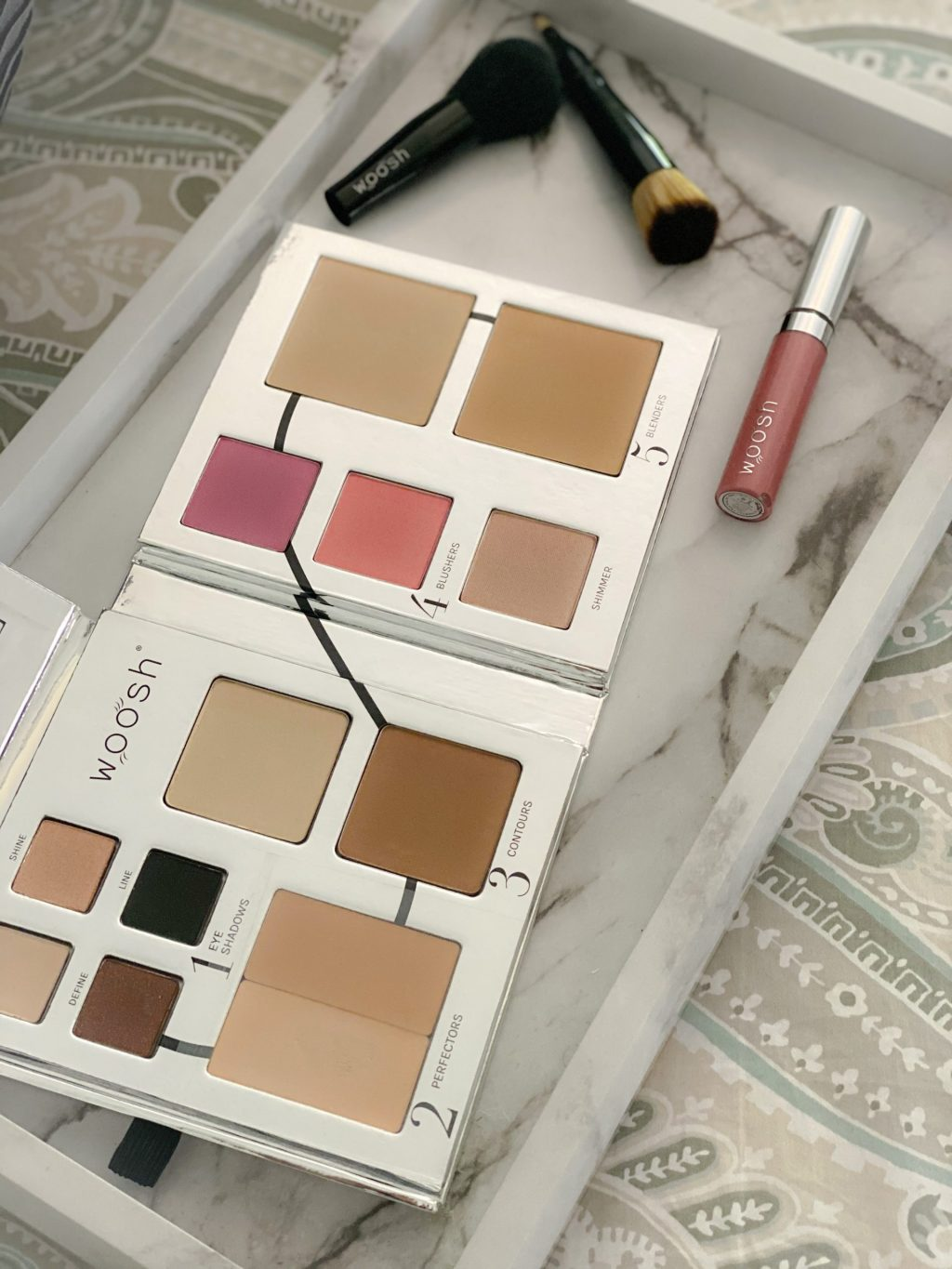 makeup palette, pink lip gloss and black makeup brushes on white and gray tray