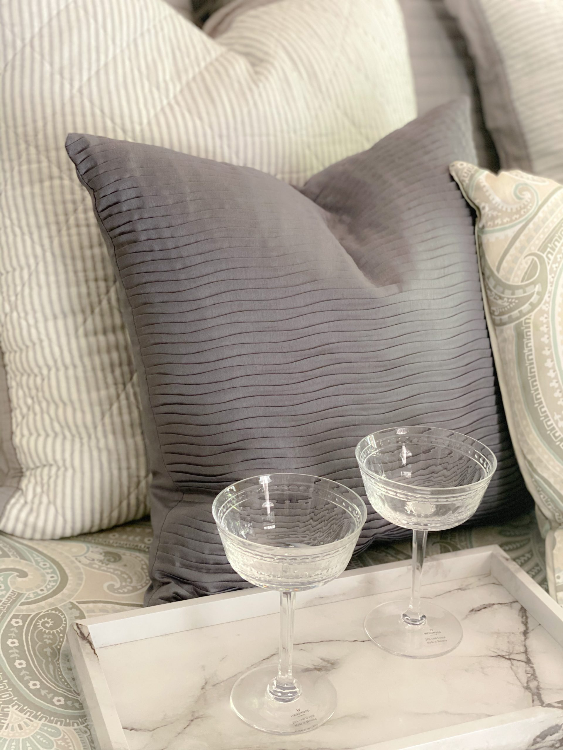 crystal cocktail glasses on white marble tray on white and gray bedding