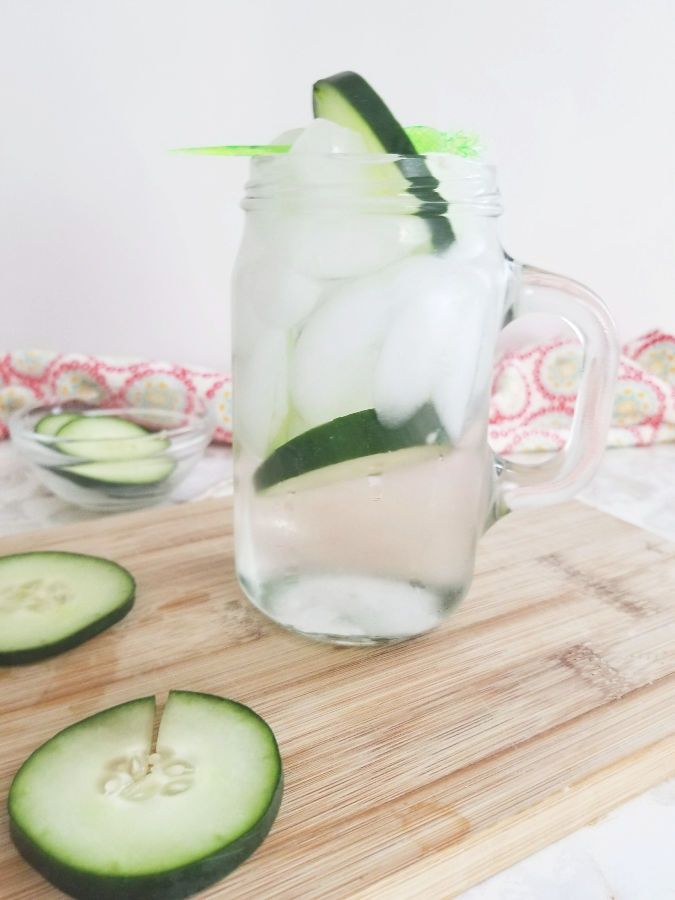 clear glass with handle filled with ice and cucumbers sitting on top of light wood cutting board with a pink and white print napkin in the background