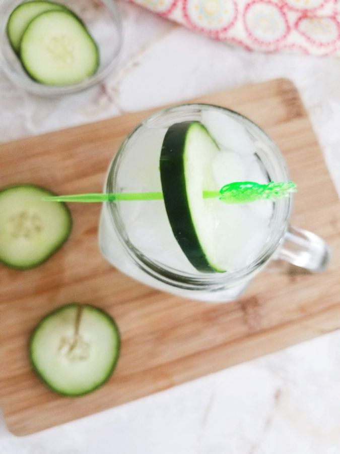 white clear glass with handle filled with ice and cucumber on top of light wood cutting board with cucumbers on it