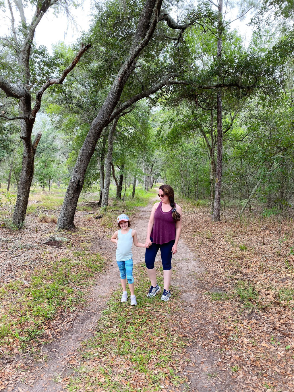 woman wearing maroon top and navy leggings holding hands with little girl in a blue top and leggings in the woods
