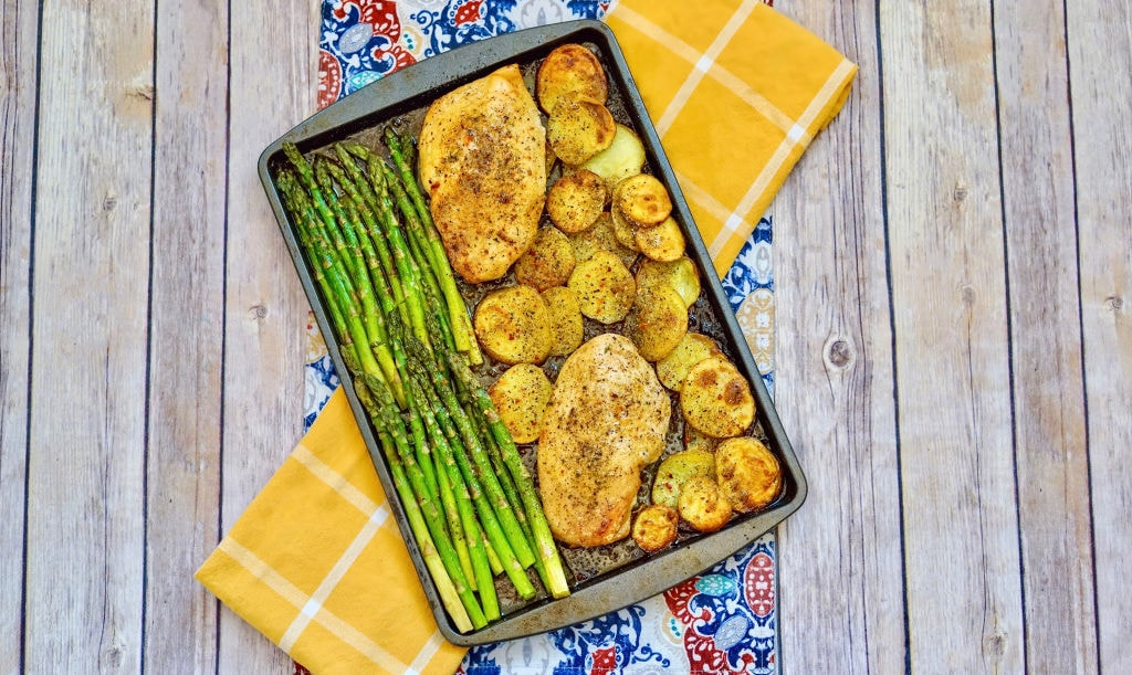 sheet pan with chicken, potatoes and asparagus on top of yellow plaid and red and blue floral dish towels