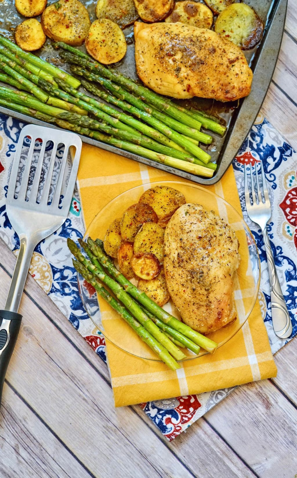 spatula next to clear plate with chicken, potatoes and asparagus on top of yellow plaid dish towel and sheet pan with more chicken, potatoes and asparagus