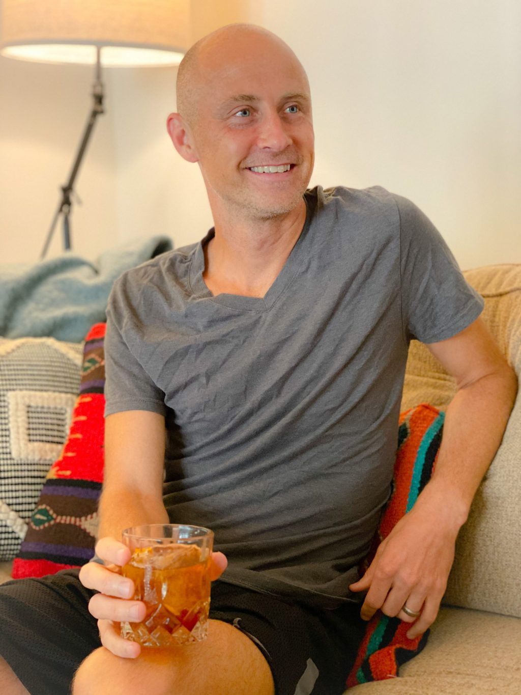 bald man wearing gray t-shirt sitting on a brown couch holding an old fashioned cocktail in a glass