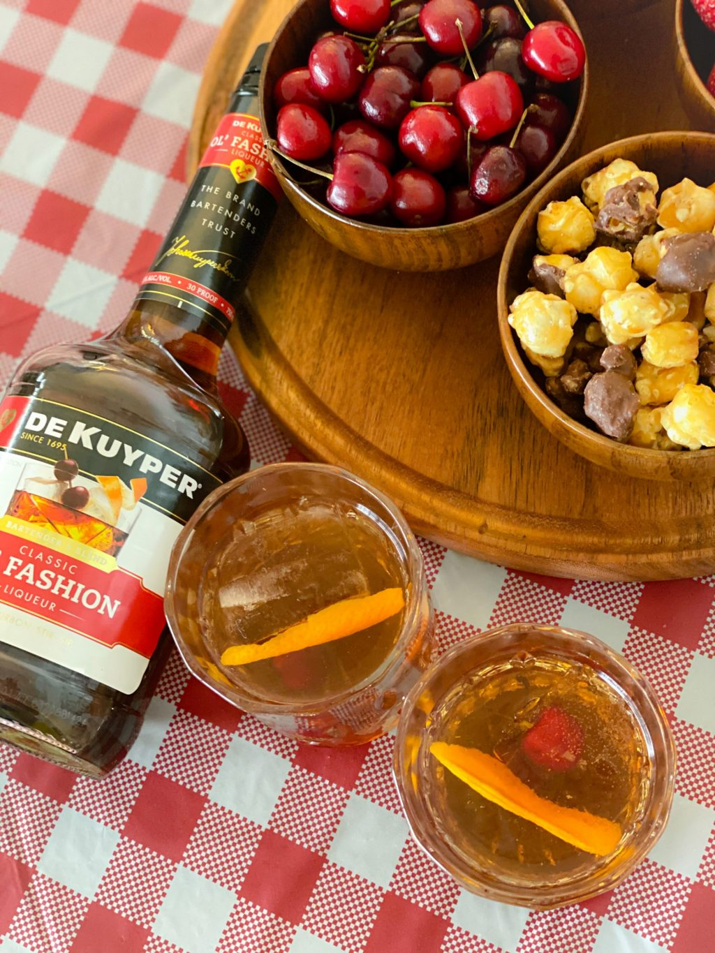 old fashioned liqueur and old fashioned cocktails in glasses on top of red and white tablecloth next to wooden tray with wooden bowls full of cheeries and popcorn