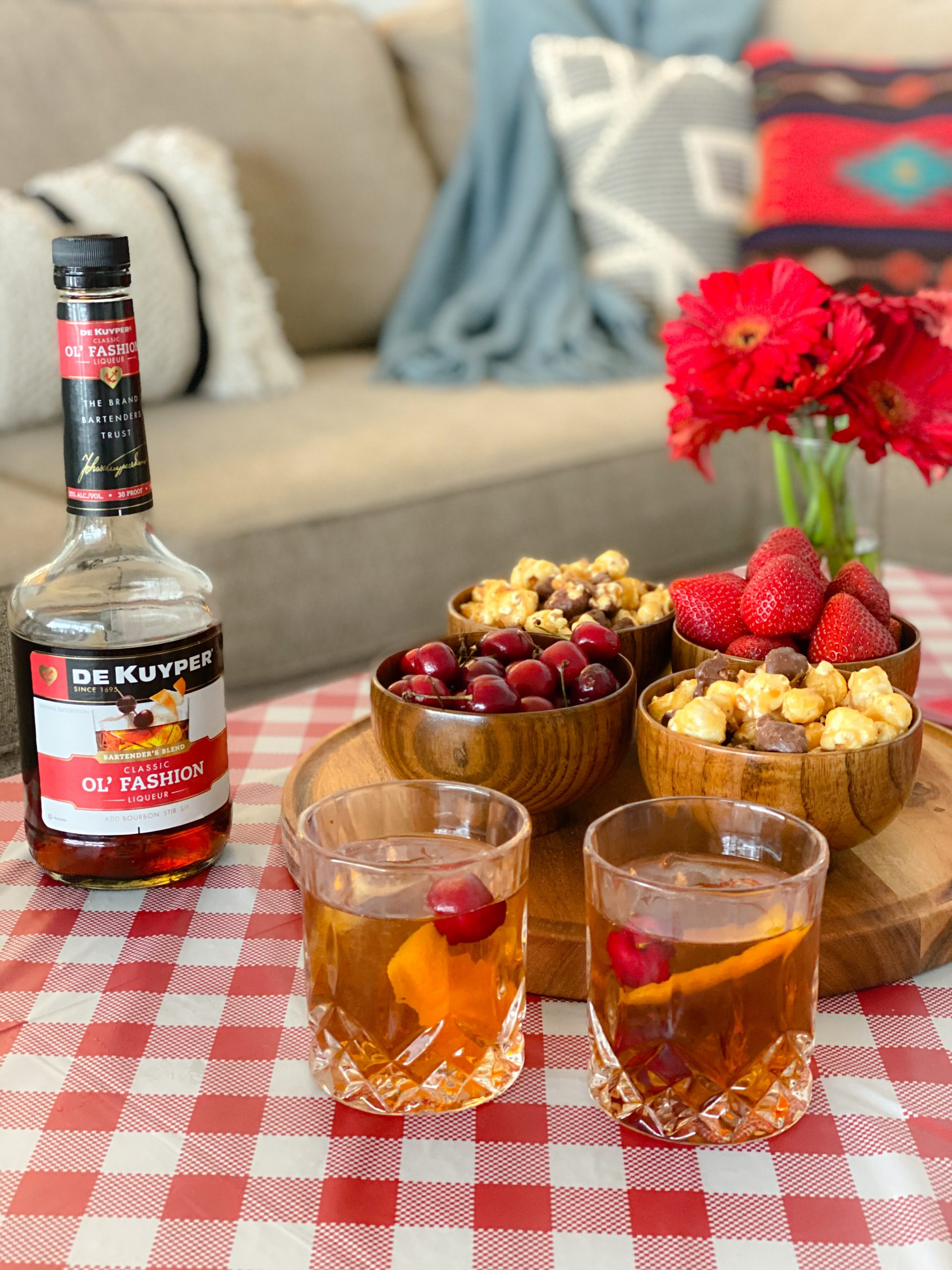 old fashioned drinks and liqueur on top of red and white check tablecloth next to wooden tray with wooden bowls filled with popcorn, cherries and strawberries next to glass of red daises